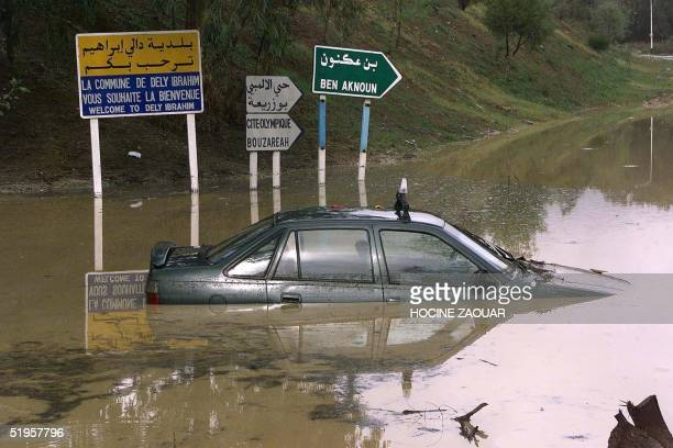 A taxi lies on a flooded road in Dely Ibrahim near Algiers after fierce storms 10 November 2001 Heavy storms have killed at least 189 people in...
