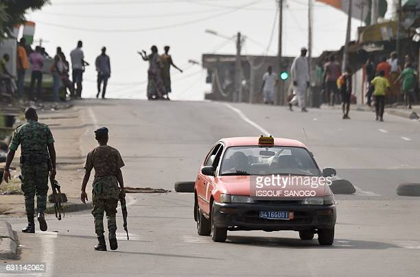 A taxi makes a uturn as soldiers walk near tyres blocking the road in the Plateau business district of Abidjan on January 7 2017 as shots were heard...