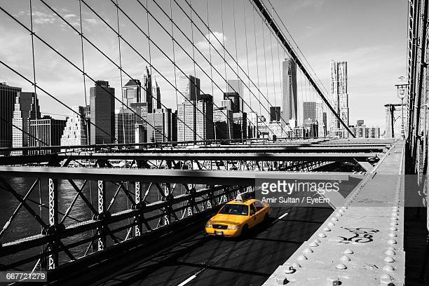 Taxi On Brooklyn Bridge Against Manhattan Skyline