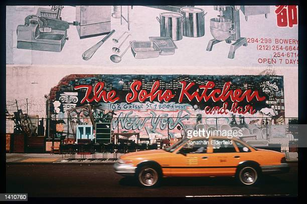 A taxi on Houston Street passes an advertisement for the Soho Kitchen and Bar in the East Village June 1 1998 in New York City Populated by residents...