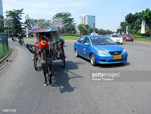 A taxi overtaking a traditional horsedrawn cart on a busy roundabout near Jakarta Indonesia Less polluting environment friendly alternative...