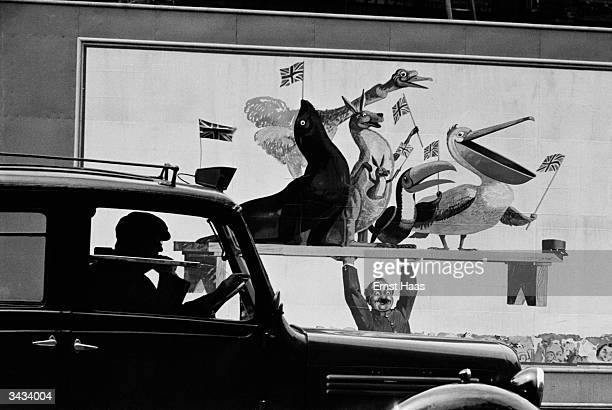 A taxi parked in front of an advertisement for Guinness showing a group of animals all waving a Union Jack and being held aloft by a zoo keeper In...