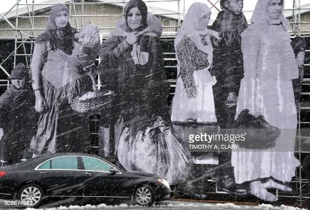 A taxi passes a new exhibit by French Street artist JR in a snowstorm outside the show during the press preview at the Armory Show March 7 2018 at...