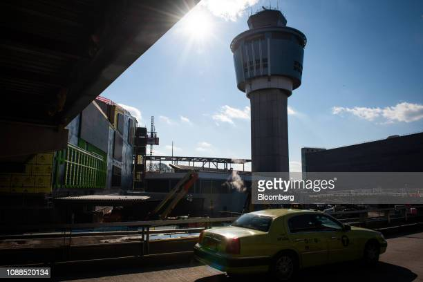 A taxi passes in front of the air traffic control tower at LaGuardia Airport in the Queens borough of New York US on Friday Jan 25 2019 The Federal...