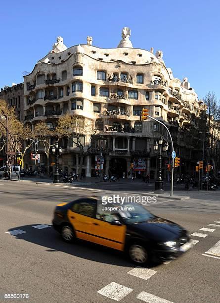 A taxi passes La Pedrera de Antoni Gaudi on March 20 2009 in Barcelona Spain