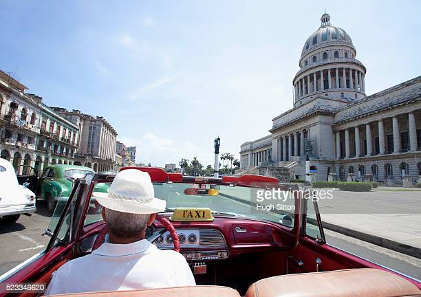 taxi passing the capitol building. havana. cuba. - hugh sitton stock pictures, royalty-free photos & images