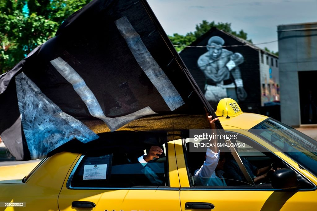 TOPSHOT - A taxi prompts a procession with the remains of boxing legend Muhammad Ali passes a mural depicting his 1965 victory over Sonny Liston on the way to Cave Hill Cemetery June 10, 2016 in Louisville, Kentucky. Thousands of people from near and far were expected to line the streets of Muhammad Ali's hometown Louisville on Friday to say goodbye to the boxing legend and civil rights hero, who mesmerized the world with his dazzling skills. / AFP PHOTO / Brendan Smialowski