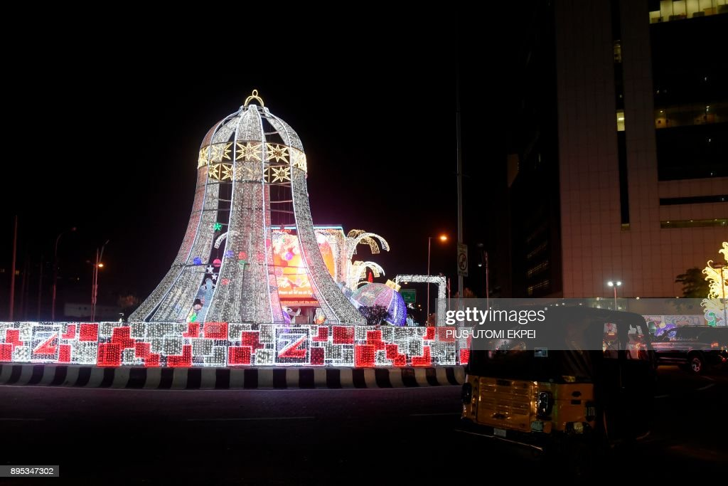 a taxi rick shaw drives past christmas decorations to light up the streets of lagos on december 18 2017 lagos metropolis is wearing a new look as
