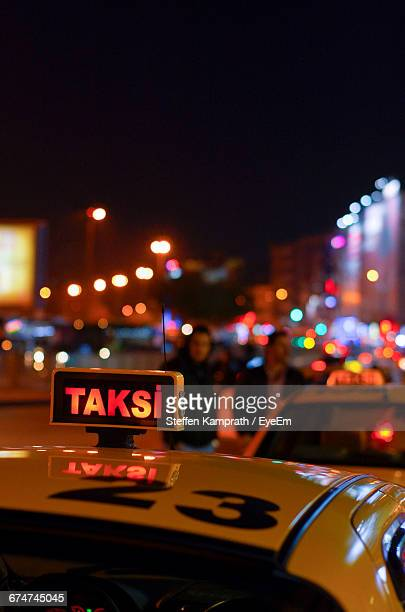 Taxi Sign Against Defocused Lights At Night