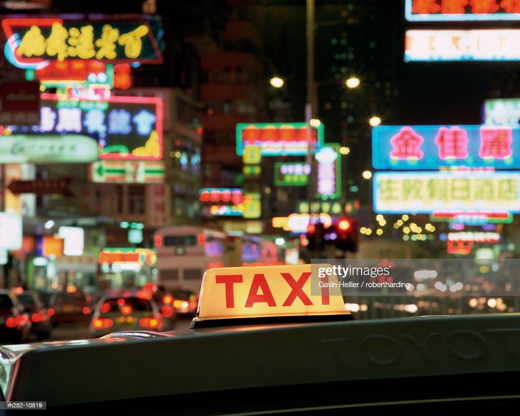 Taxi sign and neon lights at night on Nathan Road, Kowloon, Hong Kong, China, Asia : Foto de stock