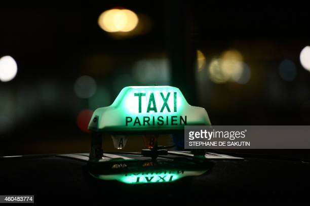 A taxi sign is pictured on December 15 2014 at the ParisOrly Airport in Orly outside Paris before a demonstration of taxi drivers to protest against...