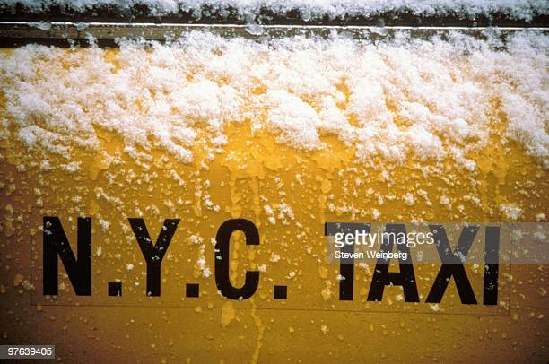 NYC taxi sign on door covered in snow