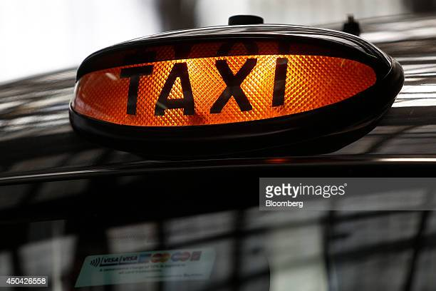 A 'Taxi' sign sits illuminated on the roof of a black London taxi cab outside Waterloo train station ahead of a protest against Uber Technologies...