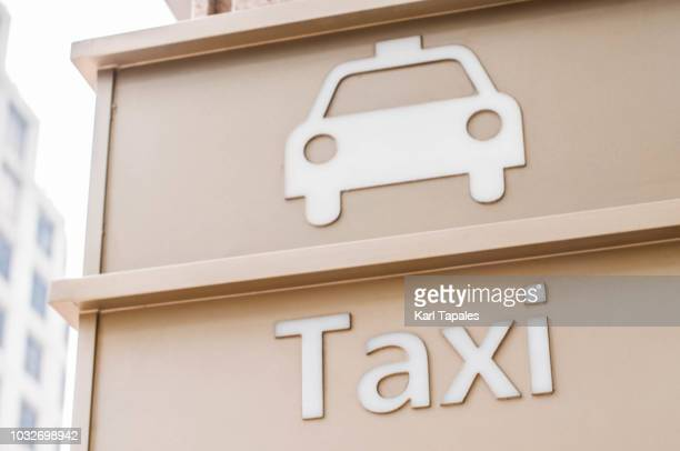 Taxi sign written on a white wall