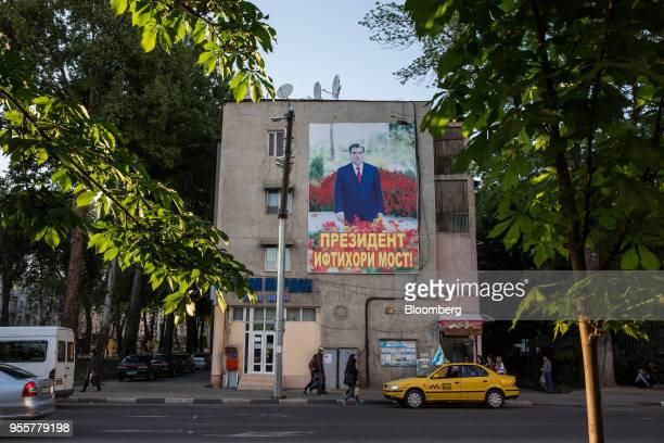 A taxi sits parked below a banner featuring an image of Tajikistan President Emomali Rahmon displayed on a building in Dushanbe Tajikistan on...