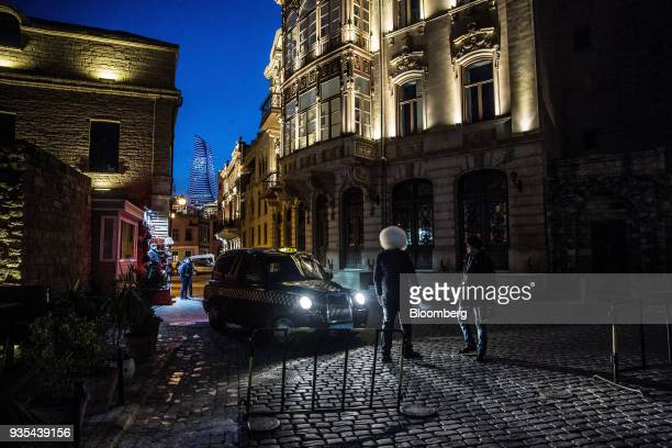 A taxi stands parked in a cobbled street as the Flame Towers stands in the background at night in the Old City of Baku Azerbaijan on Friday March 16...