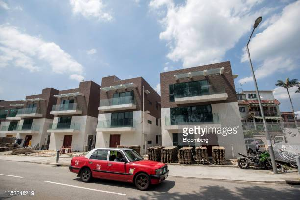 A taxi travels past newly constructed houses in a village in the rural New Territories in Hong Kong China Friday June 14 2019 Under the socalled...