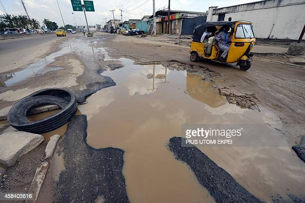 Taxi tricyclists try to avoid waterlogged potholes on Apapa Oshodi expressway that leads to Apapa ports West Africa's busiest and largest container...