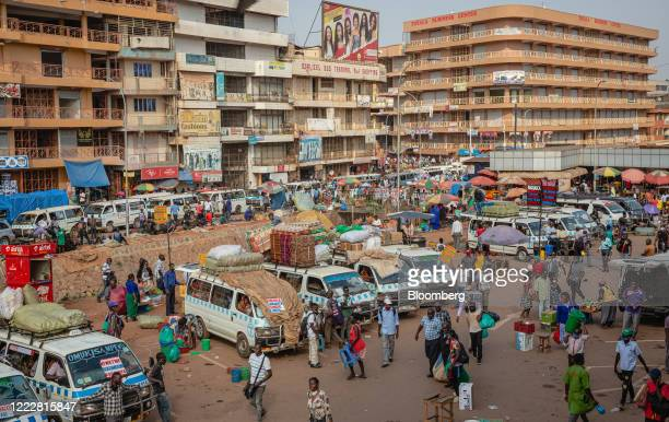 Taxi vans sit parked as passengers walk through New Taxi Park in downtown Kampala, Uganda, on Tuesday, June 23, 2020. Uganda has enforced...
