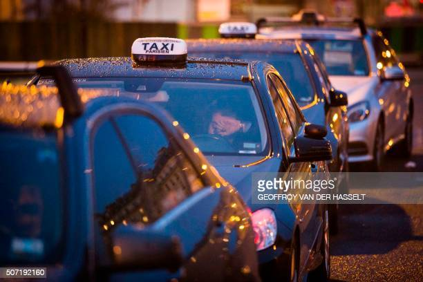 Taxicabs line up during a protest at Porte Maillot in Paris against private hire services on January 28 2016 Taxi drivers are angry at competition...