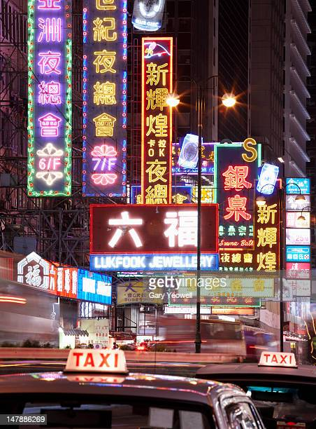 taxis along neon lit street in hong kong - tsim sha tsui stock pictures, royalty-free photos & images