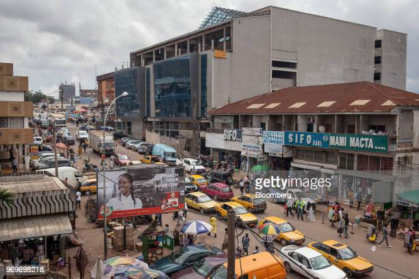 Taxis and automobiles make their way along the street by Yaounde's central market in Yaounde, Cameroon, on Monday, June 4, 2018. Cameroon adjusted...