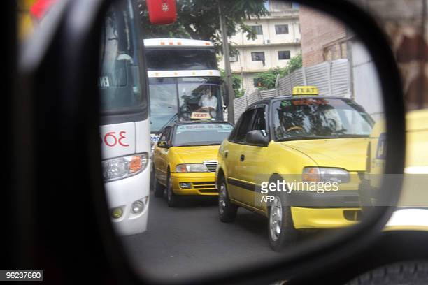 Taxis and buses are seen through a wing mirror in the streets of Asuncion on January 28 2010 AFP PHOTO / Jorge Romero