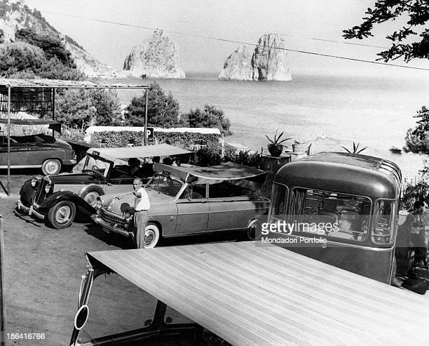 Taxis and buses are waiting for tourists in a car park on the background the sea and the Faraglioni the wellknown towering blocks of stones Capri...