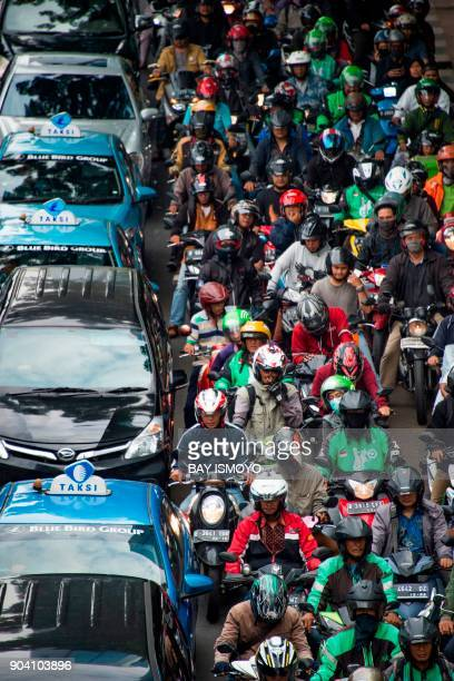 Taxis and motorcyclists are seen in heavy traffic during the afternoon rush hour in Jakarta on January 12 2018 / AFP PHOTO / BAY ISMOYO