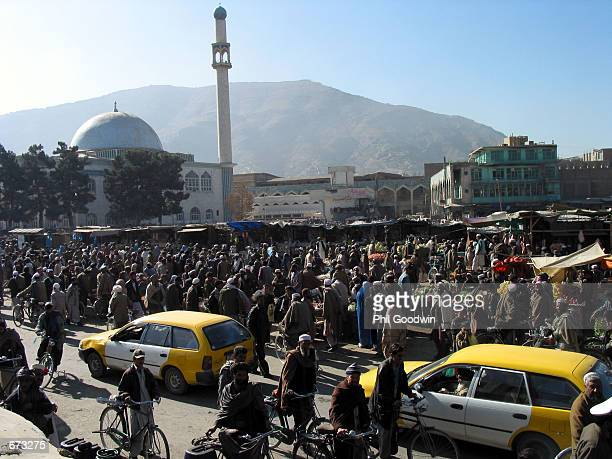 Taxis and pedestrians pack the main market of Kabul November 25 2001 in Afghanistan Market activity was the same under Taliban rule but people are...