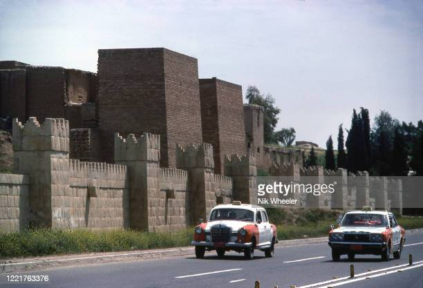 Taxis drive along road beside restored walls of ancient Akkadian and net-assyrian city pf Nineveh which from 662-612 BC was the largest city in the...