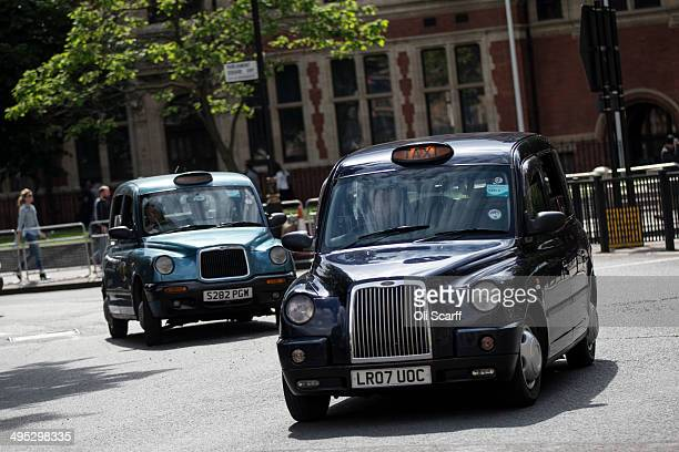 Taxis drive on the streets of Westminster on June 2 2014 in London England The controversial mobile application 'Uber' which allows users to hail...