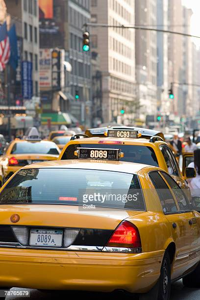 Taxis driving down a street in Manhattan
