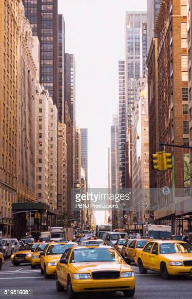 Taxis driving on city street, New York City, New York, United States