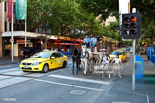 Taxis, horse and cart, cyclists and tram on Swanston Street.