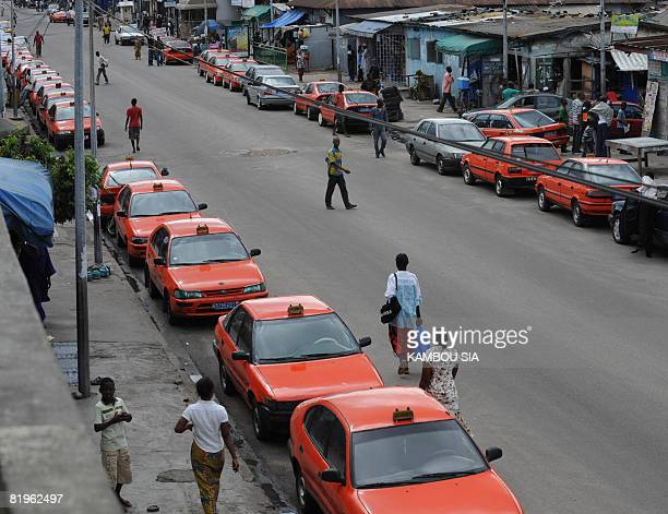 Taxi's line a street in the Treichville quarter of Abidjan on July 17 2008 Tens of thousands of people in Ivory Coast's capital Abidjan were forced...