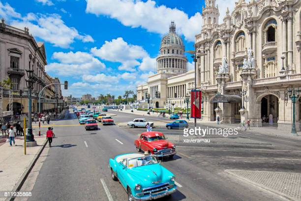 taxis on street by capitolio building in havana - old havana stock pictures, royalty-free photos & images