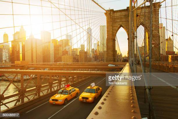 taxis on the brooklyn bridge at sunset in new york - brooklyn bridge stock pictures, royalty-free photos & images