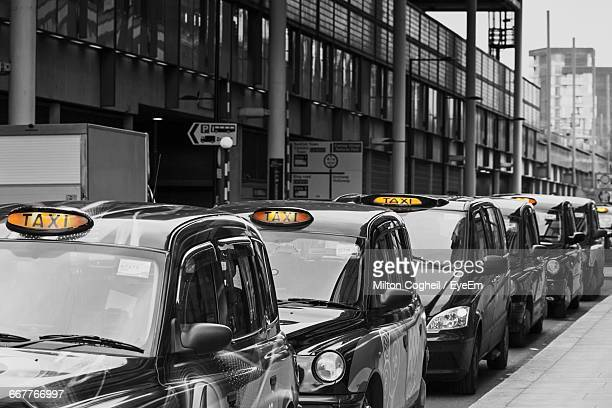Taxis Parked By Building On Street During Sunny Day