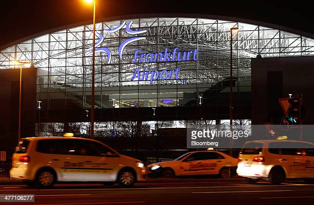 Taxis pass outside of terminal two of Frankfurt Airport operated by Fraport AG at night in Frankfurt Germany on Thursday March 6 2014 Fraport said...