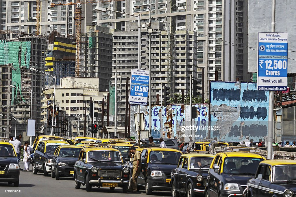 Taxis wait in line as residential buildings stand in the Chembur area of Mumbai, India, on Sunday, Aug 4, 2013. India's purchasing managers index (PMI) for services figures for July are scheduled for release on Aug. 5. Photographer: Dhiraj Singh/Bloomberg via Getty Images