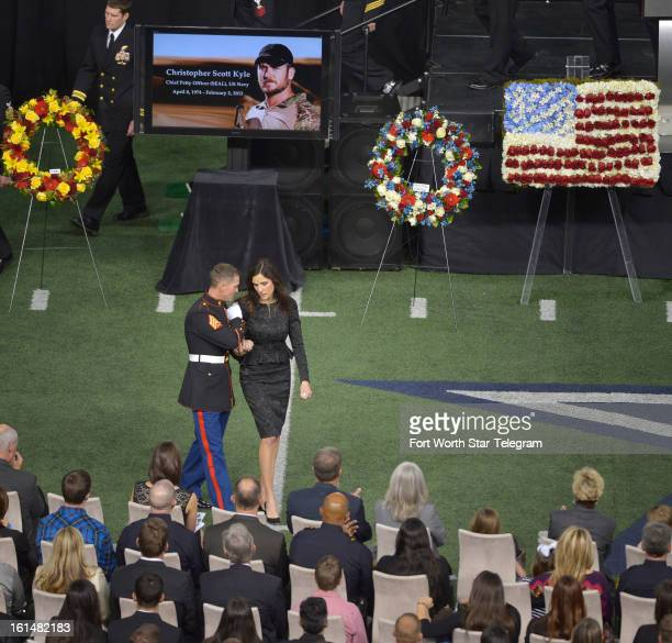 Taya Kyle is escorted back to her seat after addressing the audience at the funeral of her husband Chris Kyle at Cowboys Stadium in Arlington Texas...
