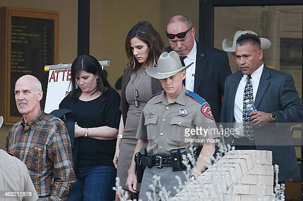 Taya Kyle wife of slain Navy SEAL Chris Kyle is escorted to a waiting vehicle as she leaves the Erath County Donald R Jones Justice Center February...