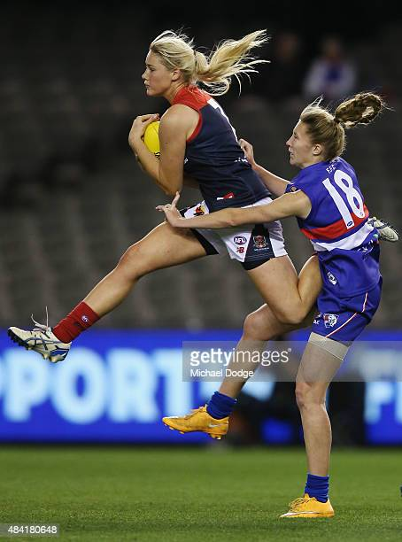Tayla Harris of the Demons marks the ball against Tahlia Randall of the Bulldogs during a Women's AFL exhibition match between Western Bulldogs and...