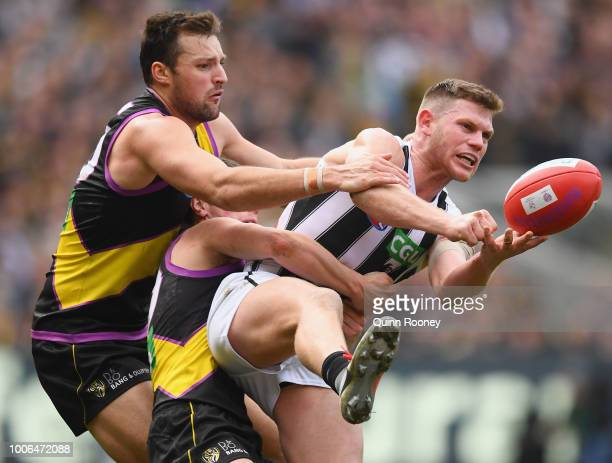 Taylor Adams of the Magpies handballs whilst being tackled by Toby Nankervis and Liam Baker of the Tigers during the round 19 AFL match between the...