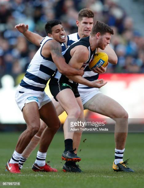 Taylor Adams of the Magpies is tackled by Tim Kelly and Zac Smith of the Cats during the 2018 AFL round eight match between the Collingwood Magpies...