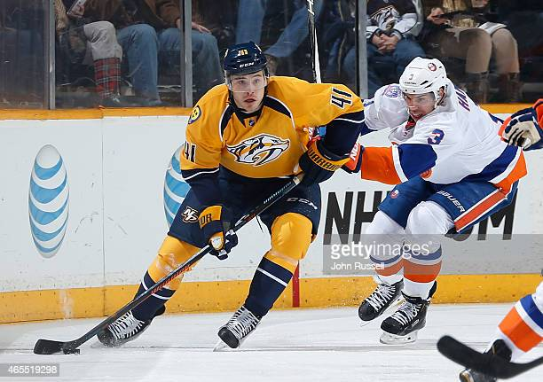 Taylor Beck of the Nashville Predators skates against Travis Hamonic of the New York Islanders during an NHL game at Bridgestone Arena on March 5...