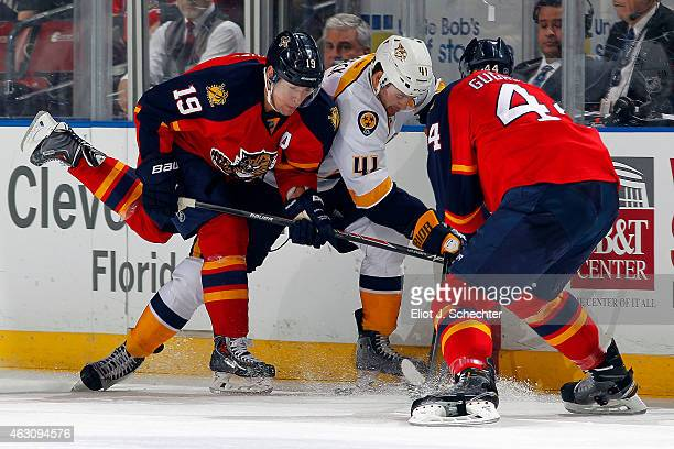 Taylor Beck of the Nashville Predators tangles with Erik Gudbranson and Scottie Upshall of the Florida Panthers at the BBT Center on February 8 2015...