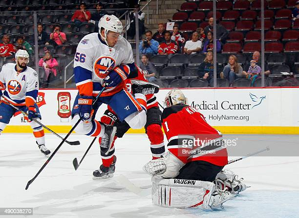 Taylor Beck of the New York Islanders jumps to avoid the puck during the first period against Keith Kinkaid of the New Jersey Devils at the...