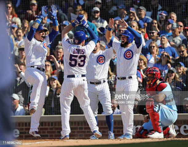 Taylor Davis of the Chicago Cubs is congratulated by teammates at the home plate following his grand slam during the fourth inning of a game against...